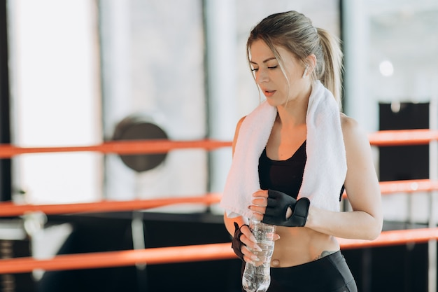 Взгляд крупного плана молодой женщины в беспроволочных наушниках имея перерыв после трудных тренировок боксерской сумкой