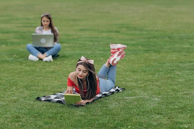 公園の緑の草にコンピューターを使用して女性。フリーランスの屋外作業やリラクゼーションコンセプト