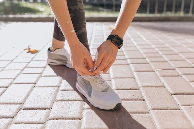 Изображение крупного плана женщины спортсмена связывая вверх по ее шнуркам на стенде на парке. она наклонилась и носит спортивный тренер на руке. умные часы в сторону