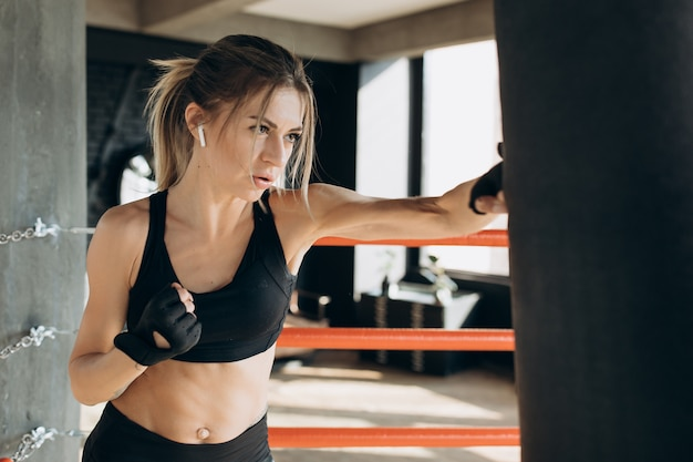 Женщина, пробивая боксерский мешок с боксерскими перчатками в тренажерном зале. понятие о спорте, фитнесе, единоборствах и людях
