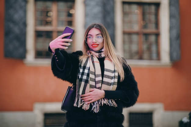 Портрет молодой счастливой женщины в зимней одежде во французском стиле, принимая селфи с смартфон