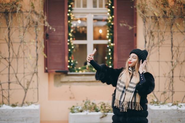 Портрет молодой счастливой женщины в зимней одежде во французском стиле, принимая селфи