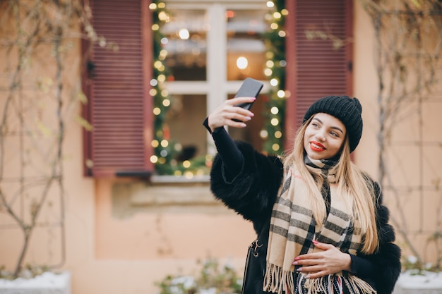 Портрет молодой счастливой женщины носить зимнюю одежду, принимая селфи