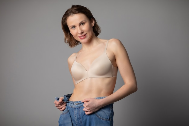 Концепция потери веса. молодая женщина показывает ее потеря веса и носить ее старые джинсы. стройная женщина в больших джинсах показывает, как худела