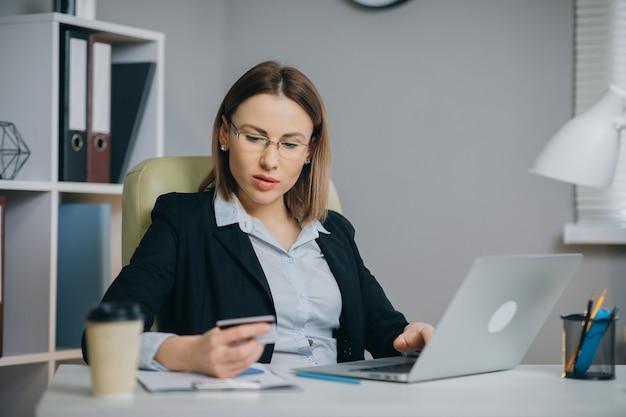 クレジットカード決済によるオンラインネットショッピングチェックアウト。ビジネスの女性がオフィスでラップトップでオンラインショッピング。