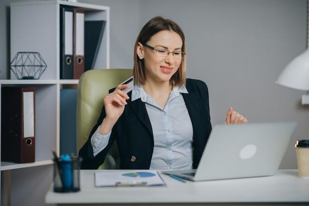 クレジットカード決済でのインターネットショッピングチェックアウト。ビジネスの女性がオフィスでラップトップでオンラインショッピング。
