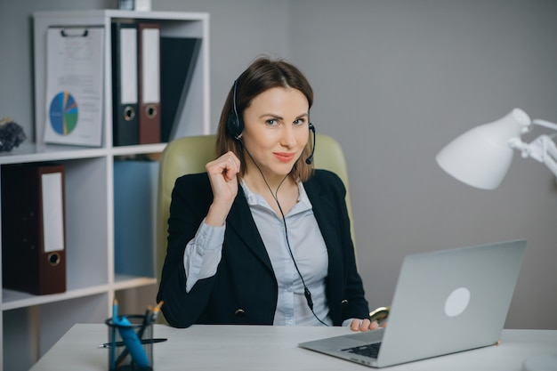 Деловая женщина в наушниках держит бумажный отчет о финансовом отчете на веб-камере и делает видео звонок в офисе