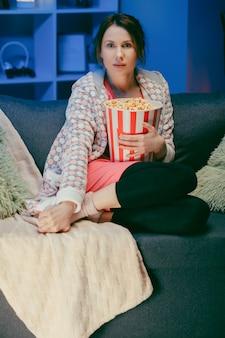 家でコメディ映画を見て幸せな美しい少女の顔。ソファーに座ってテレビを見ているミレニアル世代の女性。
