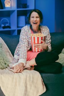 家でコメディ映画を見ている女性。ソファーに座ってテレビを見ている女性。エンターテイメントのコンセプト。