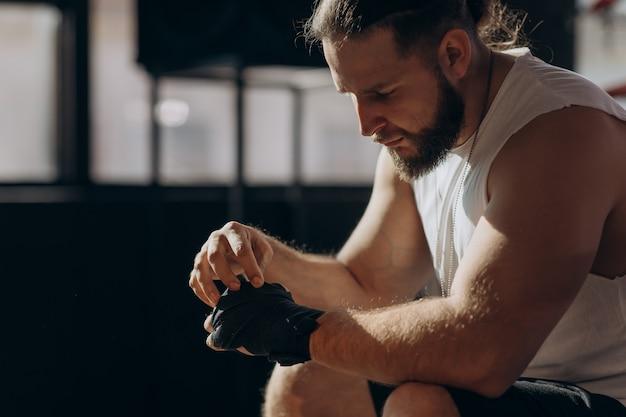 Боксер одевается на руки, сидя на краю боксерского ринга в боксерском зале, камера вращается вокруг