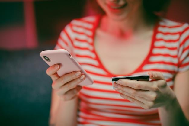 若い女性は、リビングルームのソファーに座っている間、クレジットカードでオンラインで購入しています。