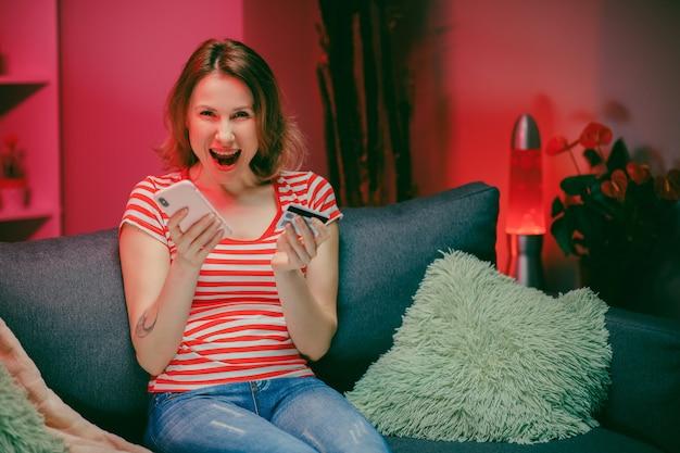 女性は、リビングルームのソファーに座っている間、クレジットカードでオンラインで購入しています。
