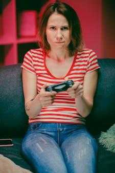 女性が夜のリビングルームでビデオゲームをプレイします。ゲーマーの女性がソファーに座って、コンソールでビデオゲームをプレイし、ワイヤレスコントローラーを使用しています。