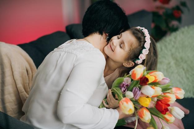 幸せな家族を抱き締めます。母の日おめでとう。小さな娘は母の日に母親を祝福します