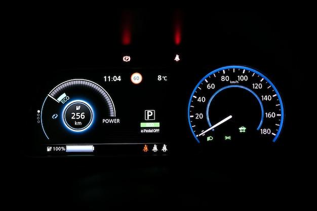 電気自動車のダッシュボードを起動しています。ボタンを追跡します。車のエンジンを始動するには、ボタンを指で押します。暗闇の中でエンジンを始動中の車のダッシュボード。バックライト付き電気自動車ダッシュボード。