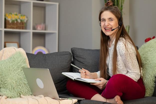 Наушники девочка-подростка нося используя компьтер-книжку сидя на кровати. счастливая школьная конференция для подростков, звонящая на компьютер для дистанционного обучения в режиме онлайн, общение с друзьями с помощью веб-камеры дома