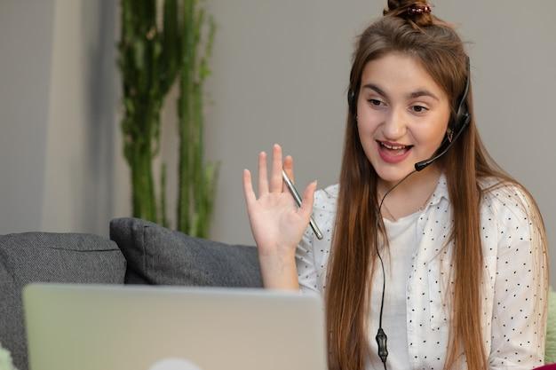 Приветствие наушников счастливой женщины нося во время видеоконференции на линии с красным компьтер-книжкой сидя в таблице в живущей комнате