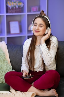 部屋でヘッドフォンで音楽を聴く女性。