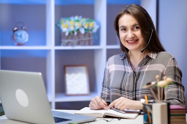 Позитивные очаровательная женщина, работа на дому. улыбающийся молодой женщины студент носить гарнитуру с помощью ноутбука для обучения онлайн-обучения в интернете у себя дома