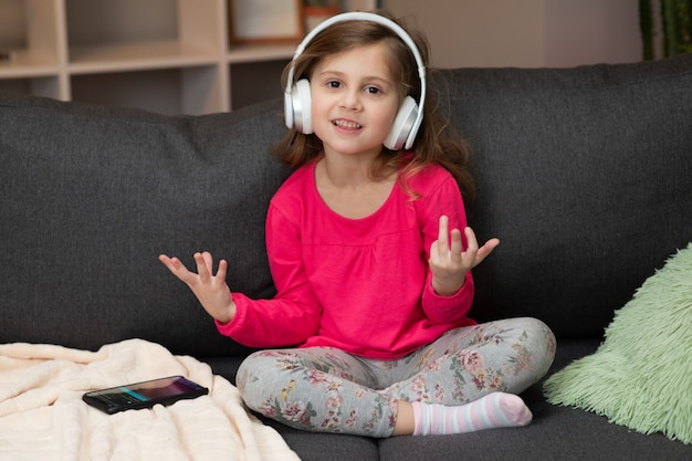 Смешная маленькая девочка в беспроводных наушниках танцует пение и движется к ритму. маленькая девочка носить наушники. малыш в наушниках. счастливая маленькая девочка слушает музыку в наушниках