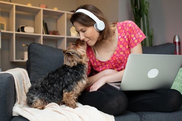 Прекрасная коричневая собака поет с ее владельцем дома, сидя на диване. веселое время вместе