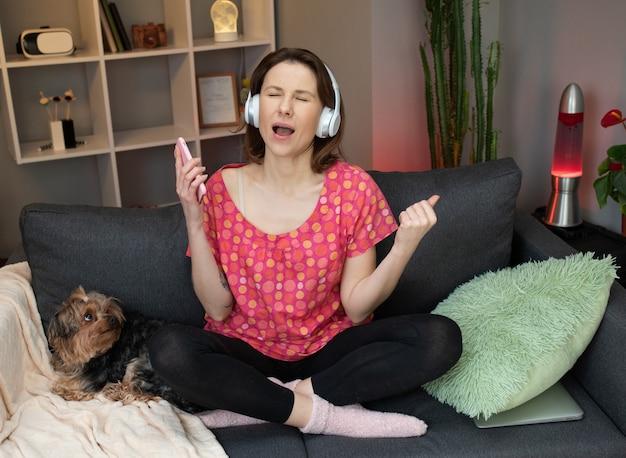 Радостная женщина в наушниках танцует на диване и используя смартфон касаясь экрана.