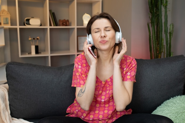 Музыка красивой молодой женщины слушая на умном телефоне, двигая к ритму пока сидящ на софе