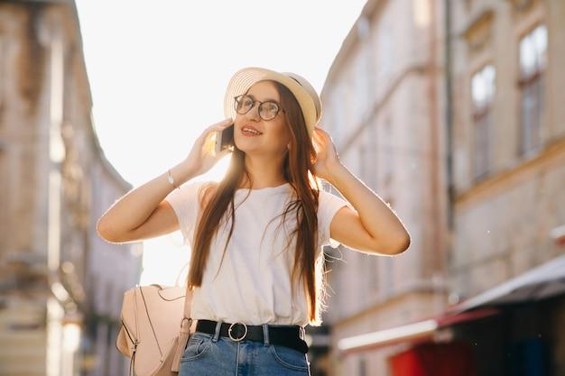 Женщина в шляпе и очках стоит на городской улице, разговаривает по мобильному телефону, улыбается, смеется.