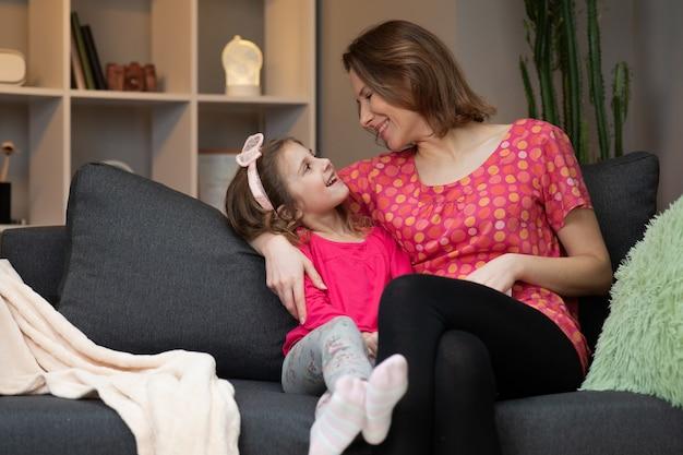 白人女性と彼女の小さな娘がソファーに座っているとテレビでコメディ映画を見て笑っています。