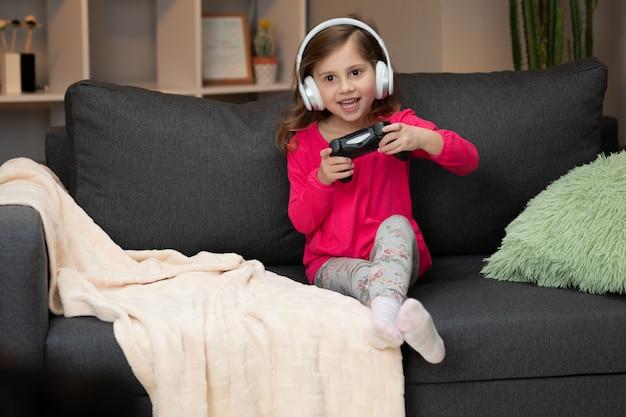 Молодая маленькая девочка сидя на софе играя видео в живущей комнате дома. возбужденных геймер девушка рука джойстик, играя в консольную игру с помощью беспроводного контроллера.