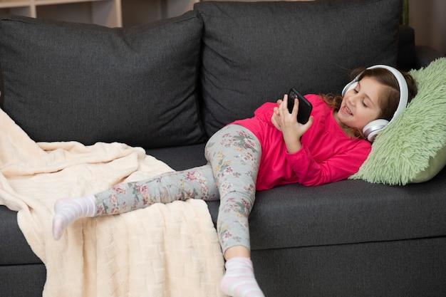Счастливая маленькая девочка в беспроводных наушниках, смех на диване и прослушивание любимой музыки с телефоном с помощью мобильного онлайн-плеера