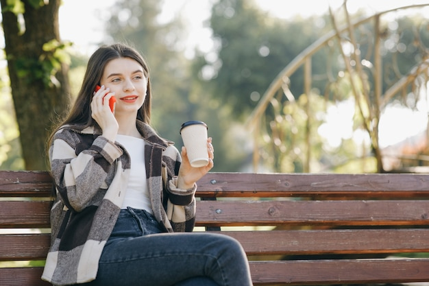 電話を使用してベンチに立っている若い美しい女性