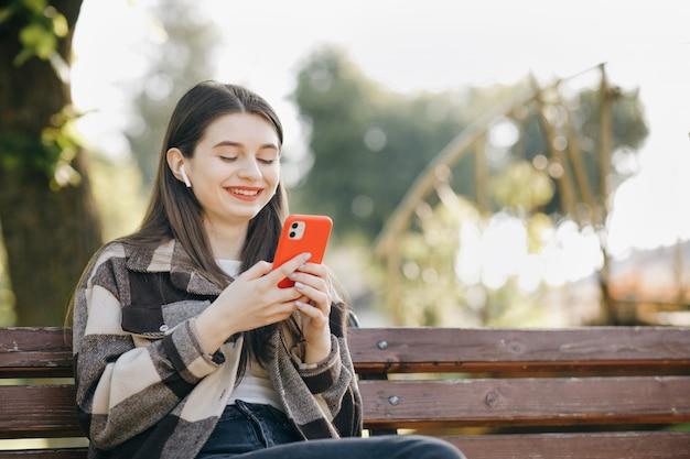 Молодая красивая женщина, стоя на скамейке, используя ноутбук