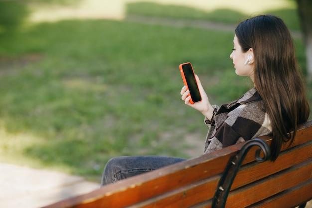 Молодая красивая женщина, стоя на скамейке с помощью телефона