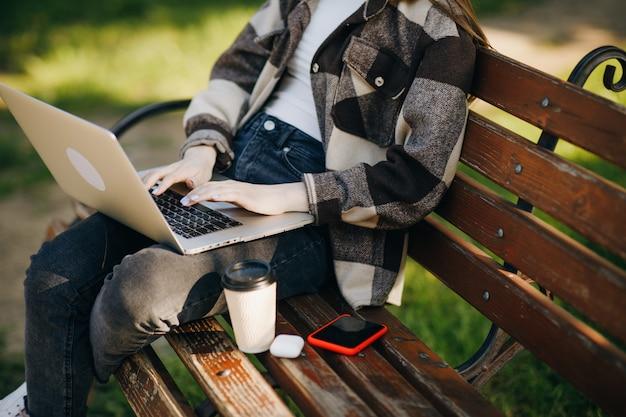 ラップトップを使用してベンチに立っている若い美しい女性