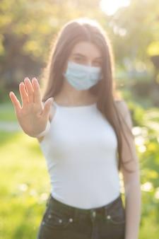 公園でフェイスマスクを持つ若い美しい女性