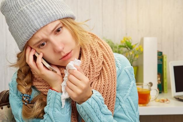 Молодая красивая больная девушка в шапке шарфа и свитера с носовым платком в руках вызывает смартфон на столе с чашкой чая, книгами и ноутбуком