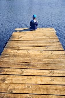 Мальчик сидит на озере деревянный пирс
