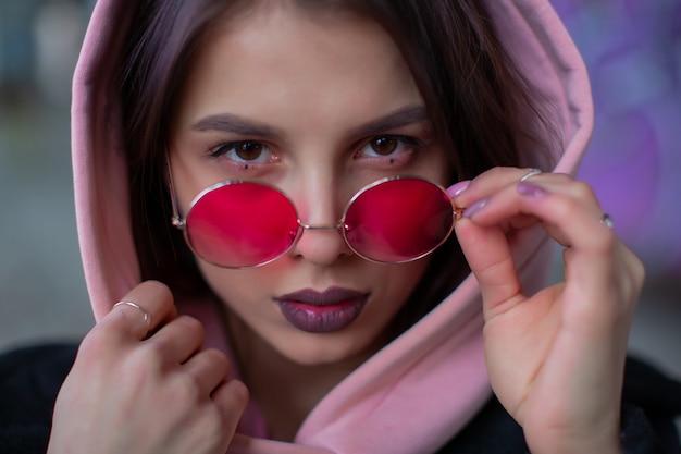 Девушка в розовом капюшоне поправляет очки