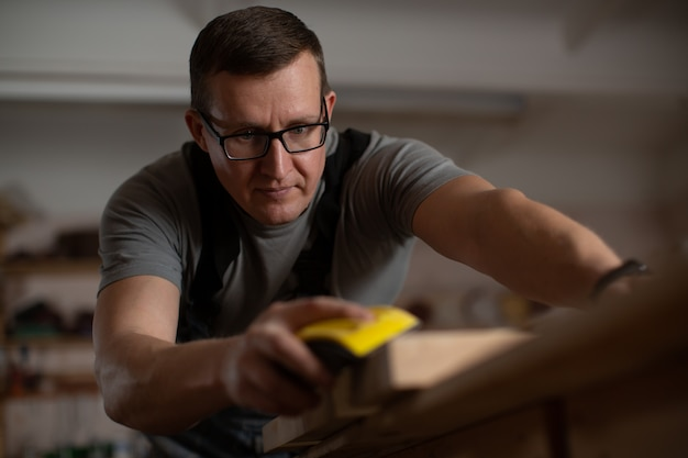 Темноволосый зрелый мужчина в очках концентрируется на очистке поверхности столешницы.
