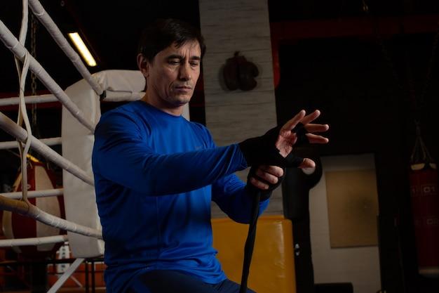 男はボクシングトレーニングセッションの準備をします。彼は包帯で手を包みます。