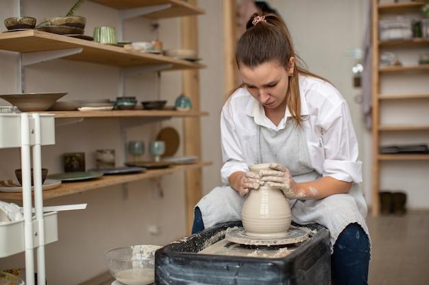 女性陶工が陶芸工房で粘土から陶器を作る。作業環境