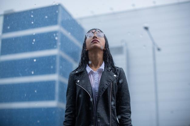Девушка стоит неподвижно под проливным дождем.
