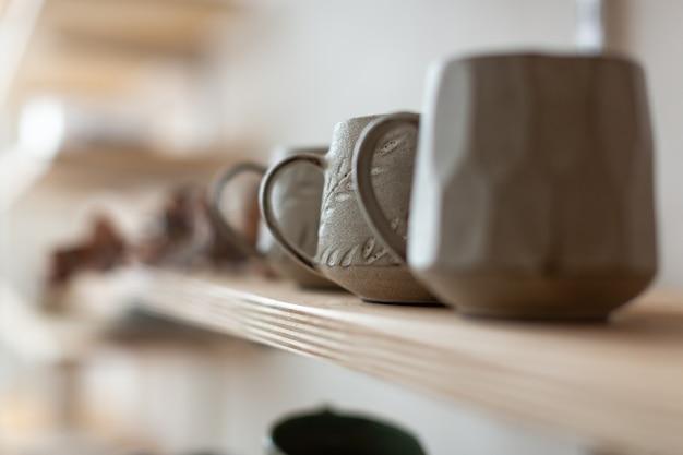 Крупный план дизайнерских керамических кружек ручной работы на полке. гончарная мастерская.