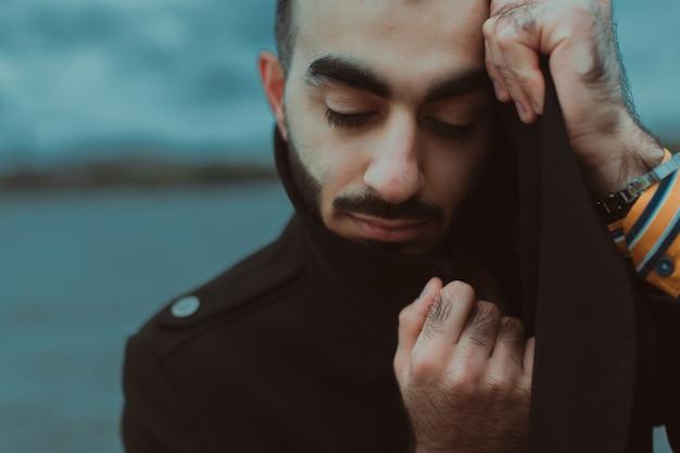 Меланхоличный молодой человек на фоне водного пейзажа.