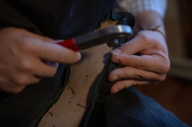 Человек делает обувь