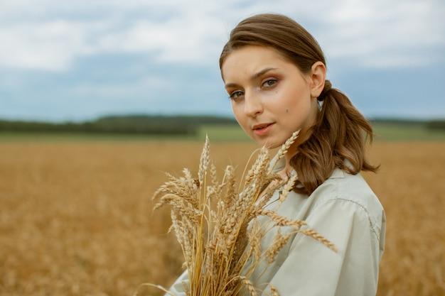 Портрет белокурой девушки с букетом ушей.