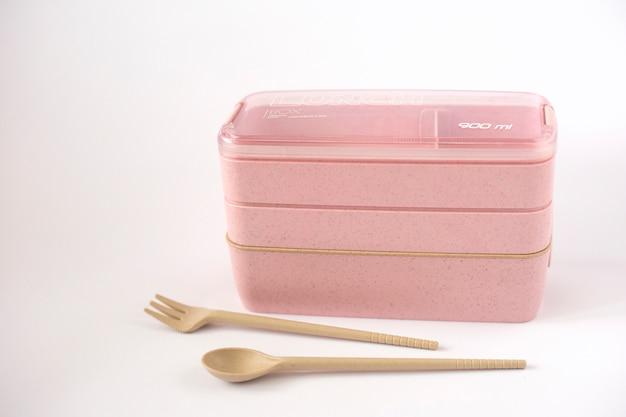 Пустая розовая коробка для завтрака на белом фоне с ложкой и вилкой