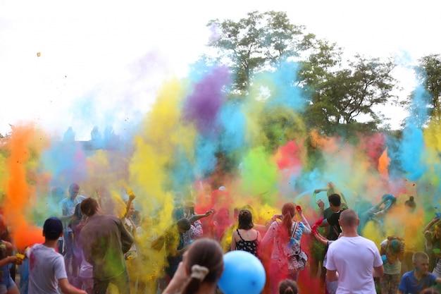 Люди бросают краски холи. холи фестиваль красок