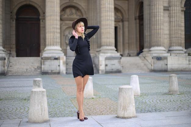 短い黒のドレスと帽子で美しい足の長いブロンドは、パリのサンシュルピス教会の前で一人で立っています。